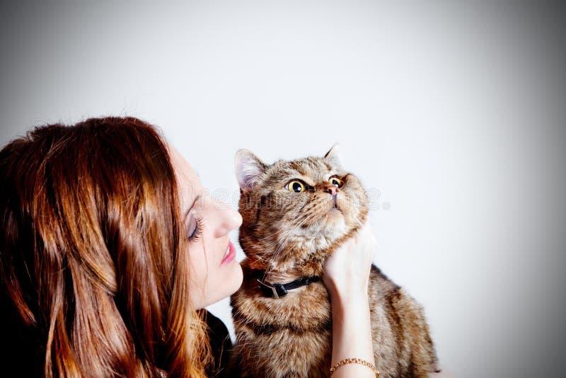 Красивая девушка с ее котом на белой предпосылке Люди и любимчики lifestyle стоковое изображение
