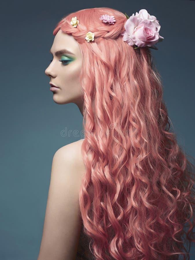 Красивая девушка с длинными розовыми волосами и цветками стоковое фото rf
