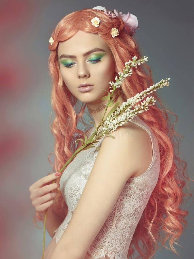 Красивая девушка с длинными розовыми волосами и цветками стоковые изображения