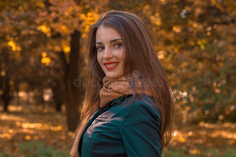 Красивая девушка с красной губной помадой на губах стоит в парке путем поворачивать ее голову к камере и усмехаться стоковое фото rf