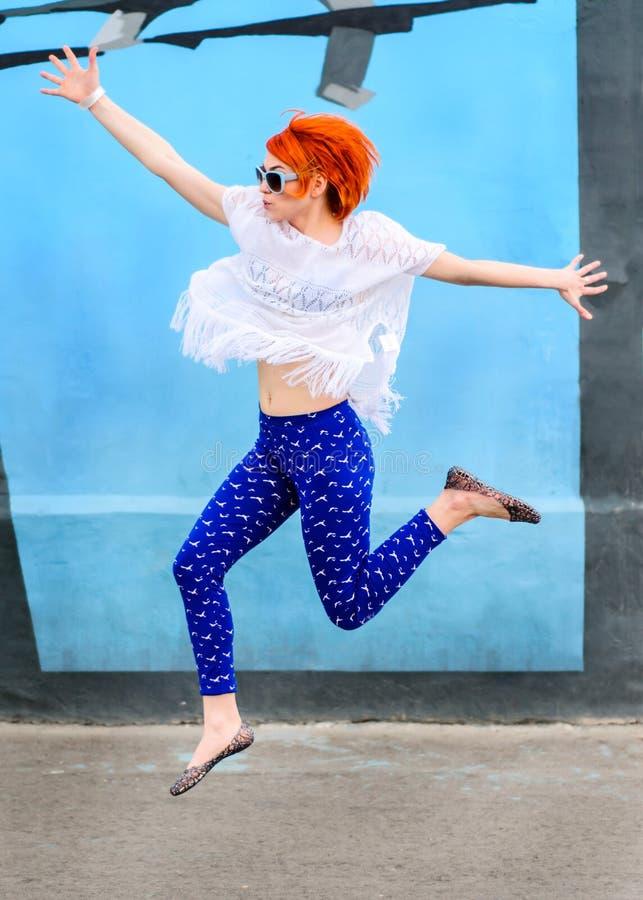 Красивая девушка с красными волосами скачет вверх в солнечный день, модель стоковое изображение