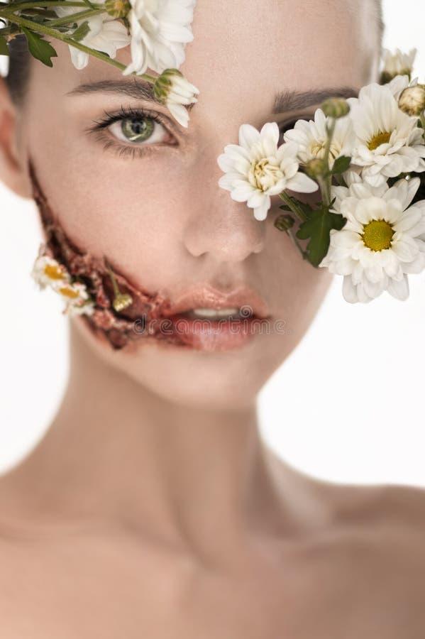 Красивая девушка с огромной раной на щеке и цветках покрывая сторону стоковая фотография rf