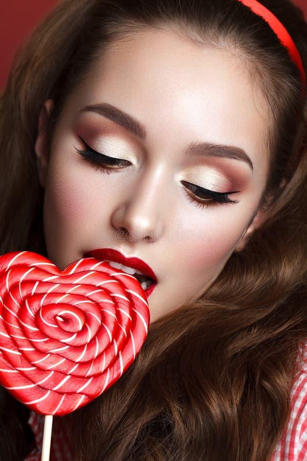 Красивая девушка с профессиональным составом и большой конфетой стоковое фото rf