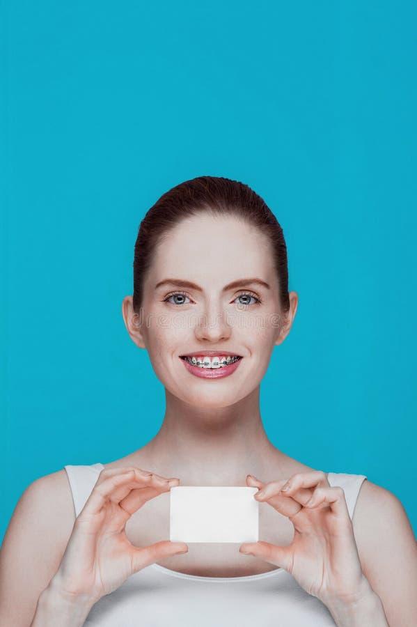 Красивая девушка с расчалками и белая карточка в руках стоковые фотографии rf
