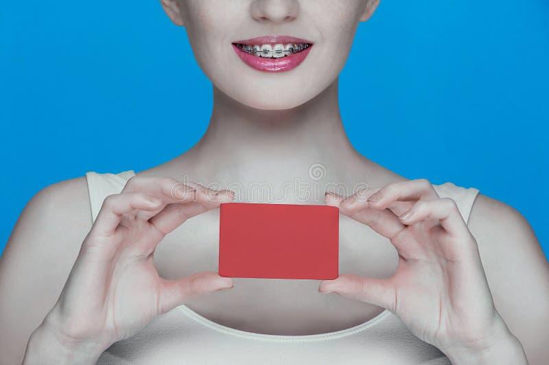 Красивая девушка с расчалками и красная карточка в руках стоковые изображения