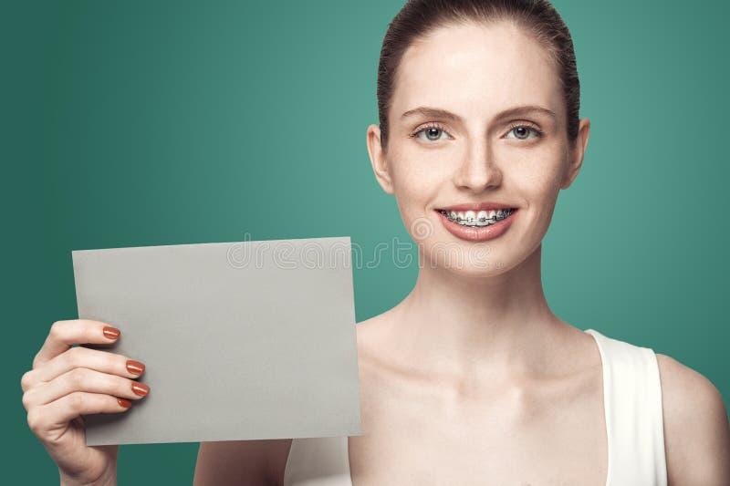 Красивая девушка с расчалками и серая карточка в руках стоковые изображения
