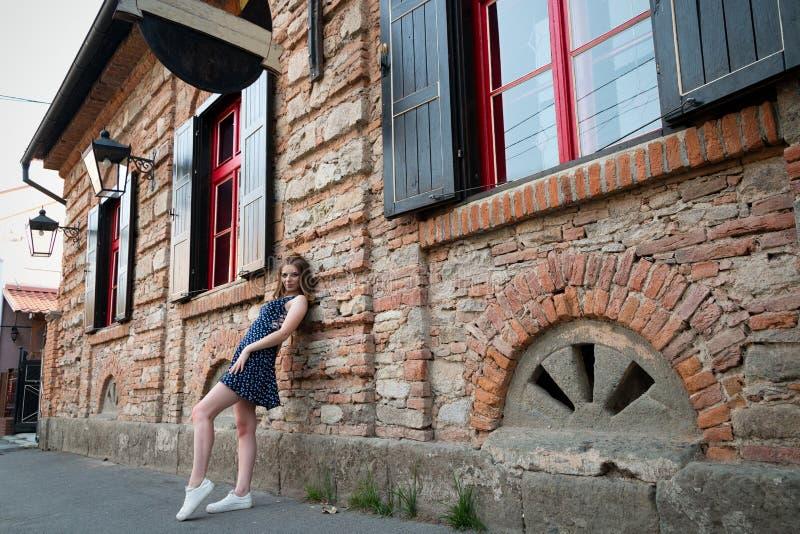Красивая девушка с составом, в темном коротком платье стоя на t стоковое фото
