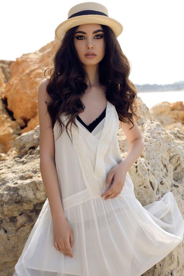 Красивая девушка с темными волосами носит вскользь элегантные одежды и шляпу представляя на береге моря лета стоковое фото