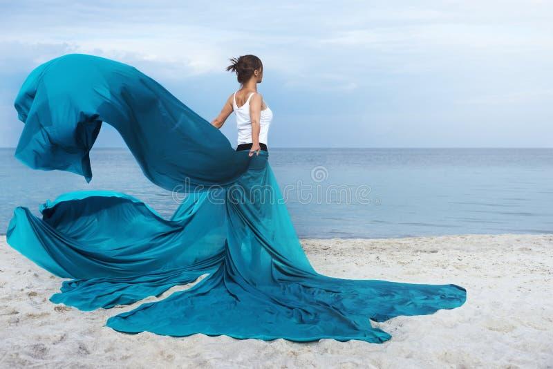 Красивая девушка с тканью на пляже стоковое изображение