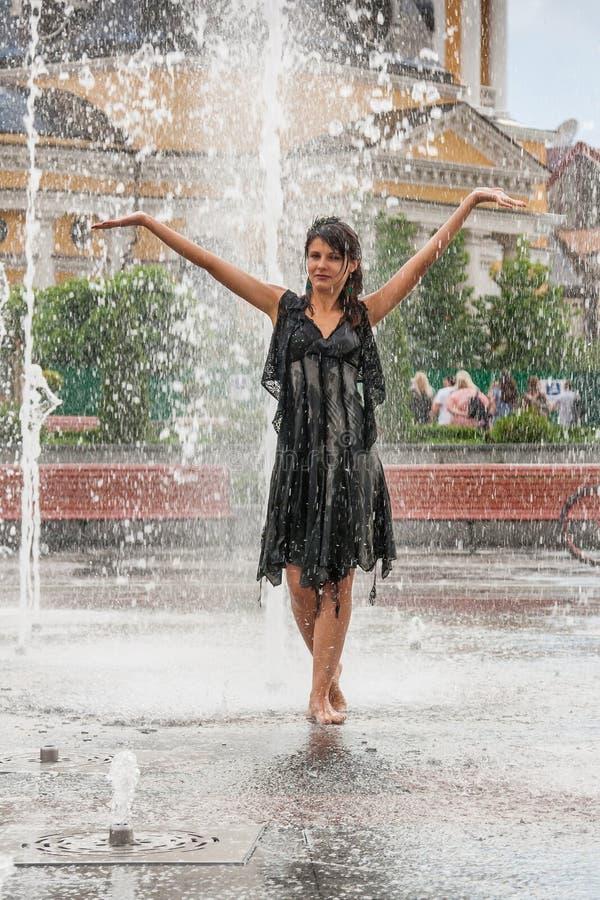 Красивая девушка танцует в фонтане стоковая фотография rf