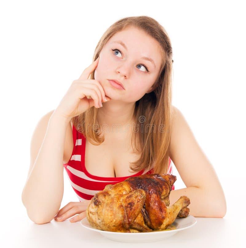 Красивая девушка думает, ест мясо стоковое изображение