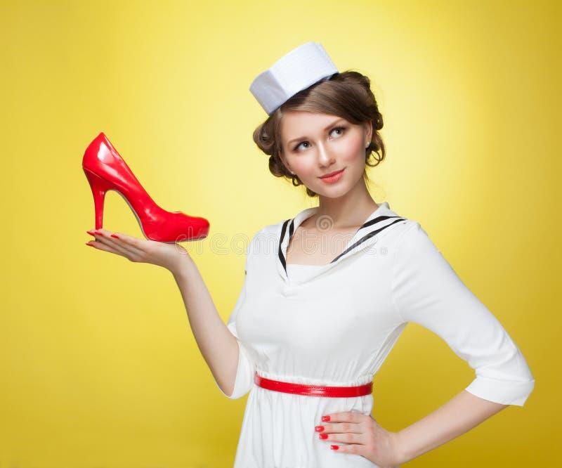 Красивая девушка штыря-вверх одела матроса держит ботинки красного цвета ладони Желтая предпосылка, конец вверх стоковое изображение