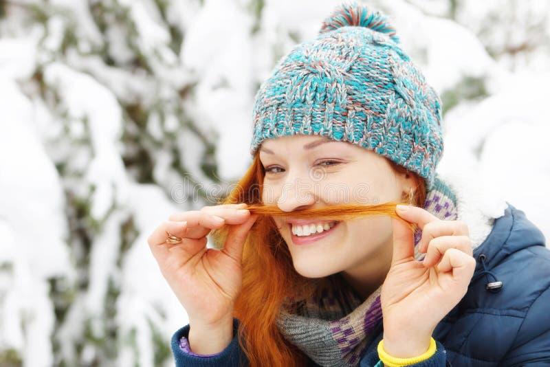 Красивая девушка redhead имеет потеху и делает усик с ее волосами стоковые фото
