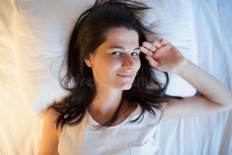 Красивая естественная молодая женщина на белой кровати над взглядом стоковые фото