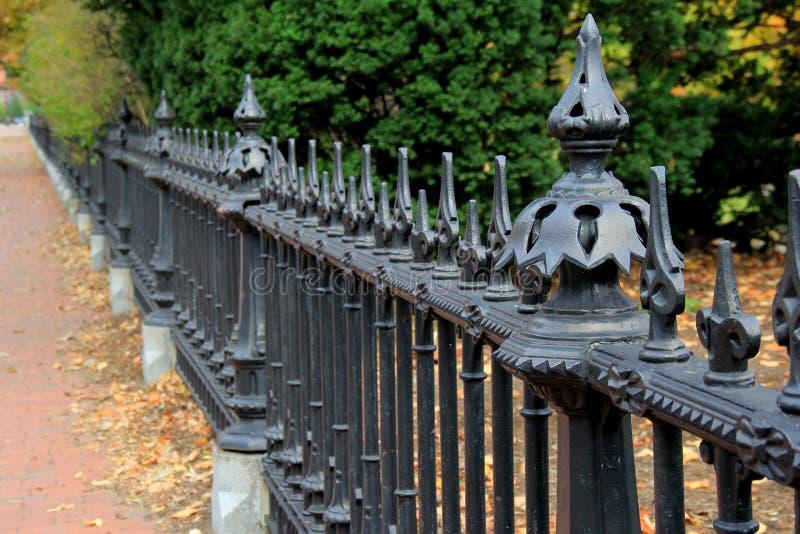 Красивая деталь черных чугунных загородки и дорожки кирпича стоковая фотография