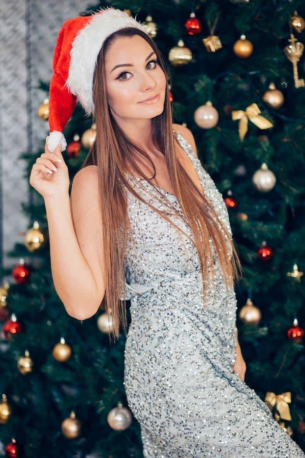 Красивая женская модельная шляпа santa носки Девушка в платье около смотреть рождественской елки стоковые фотографии rf