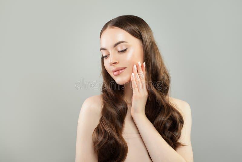Красивая женская модель с ясной кожей и коричневым вьющиеся волосы Skincare и концепция haircare стоковые фото