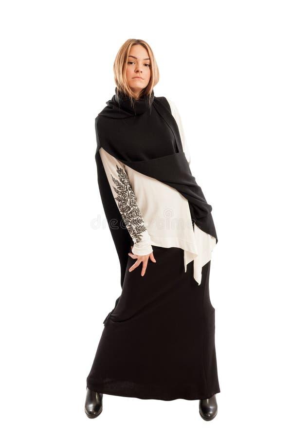 Красивая женская модель нося длинное вскользь черное платье стоковая фотография