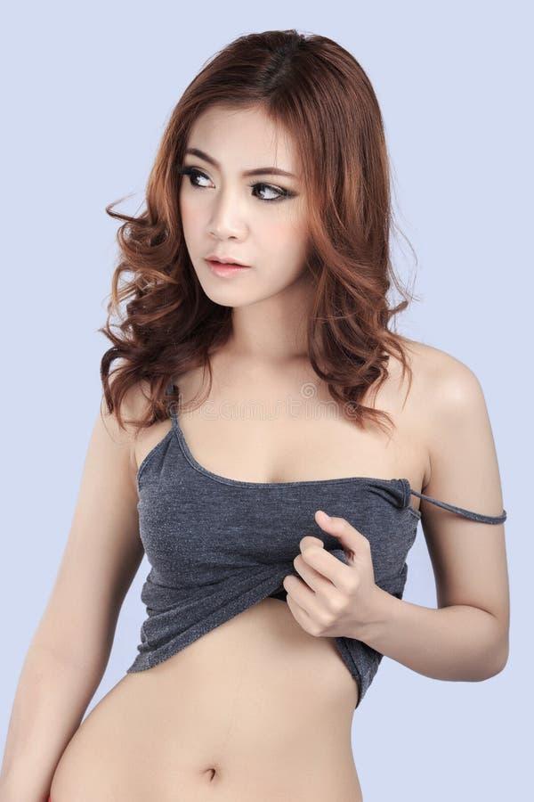 Красивая женская модель нося серую верхнюю часть танка стоковое фото