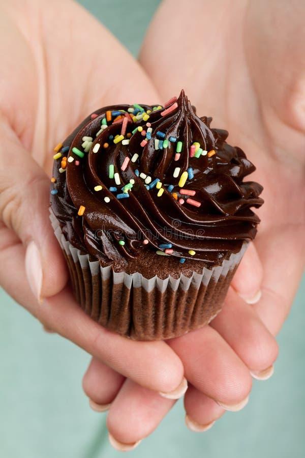 Красивая женственная рука держа вкусное аппетитное cupca шоколада стоковые фотографии rf