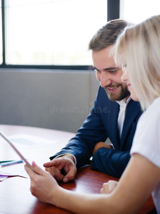 Красивая женщина бизнесмена и офиса работая с таблеткой на запачканной предпосылке Концепция встречи офиса стоковая фотография