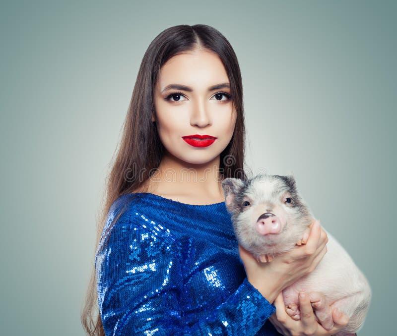 Красивая женщина брюнета в голубом платье яркого блеска держа меньшую свинью стоковые изображения