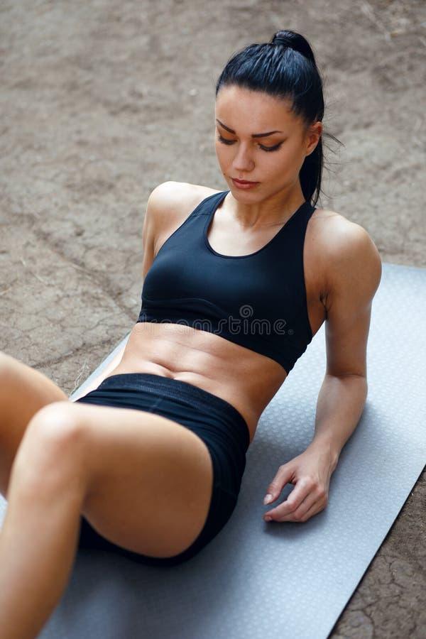 Красивая женщина брюнета в разминке sportwear снаружи, делающ тренировки прессы Вертикальный взгляд стоковое изображение