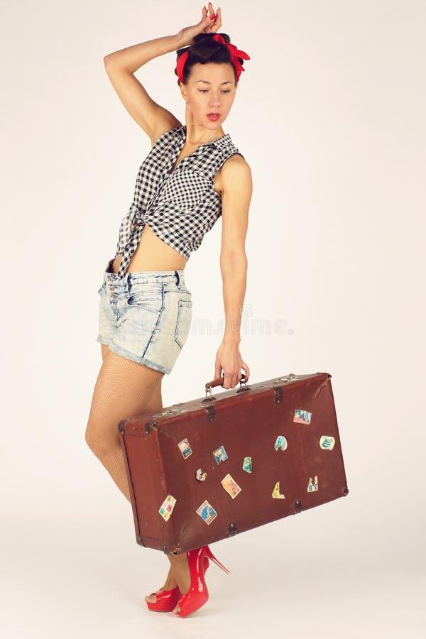 Красивая женщина брюнета в штыре вверх по стилю стоит и держит тяжелый чемодан для перемещения, белой предпосылки стоковое изображение rf