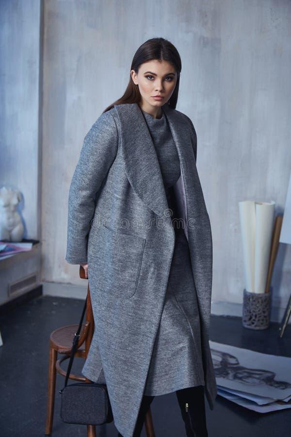 Красивая женщина брюнета носит случайные одежды стиля моды довольно смотрит на ботинки платья цвета outerwear пальто шерстей случ стоковое изображение rf