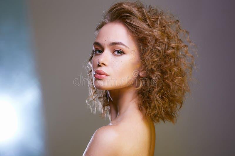 Красивая женщина брюнета с волнистыми здоровыми волосами стоковые фото