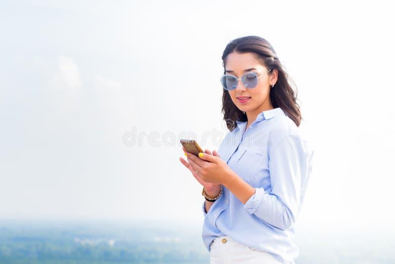 Красивая женщина брюнет в стеклах с утехой и улыбкой использует удивленный smartphone, Современная технология, применения, интерн стоковые фотографии rf