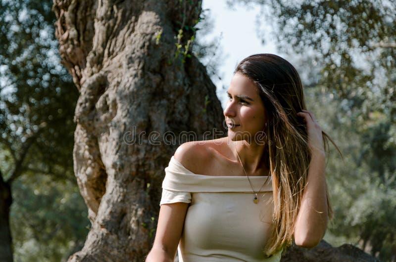 Красивая женщина брюнет касаясь ее длинным волосам Она сидит в парке на зеленой траве стоковое фото