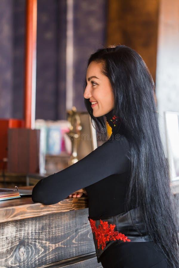 Красивая женщина брюнет при длинные волосы стоя на приеме и при улыбка смотря прочь, портрет конца-вверх стоковое изображение rf