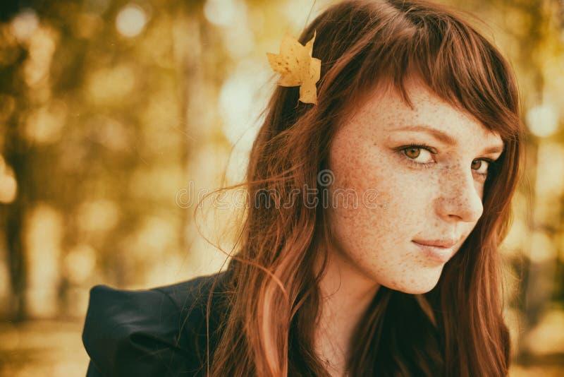Красивая женщина веснушки с красными волосами в парке падения стоковая фотография