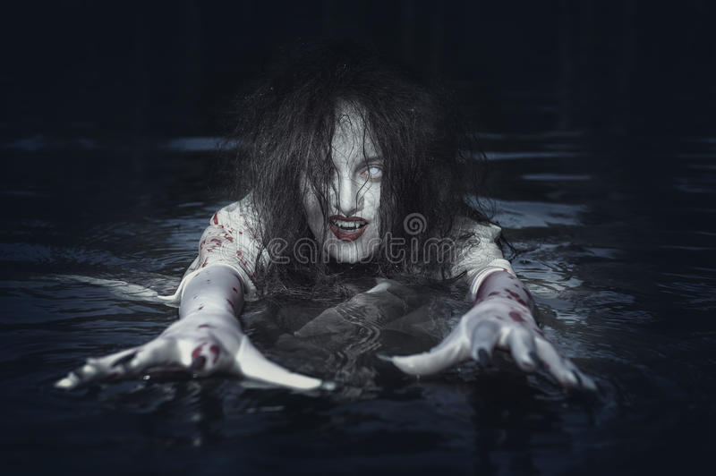 Красивая женщина ведьмы стоя в реке стоковые изображения