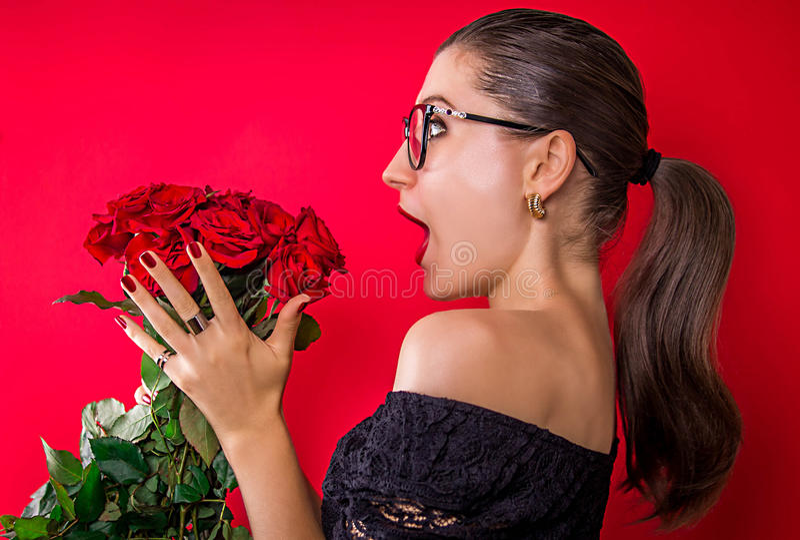 Красивая женщина возбужденная для того чтобы получить розы стоковая фотография