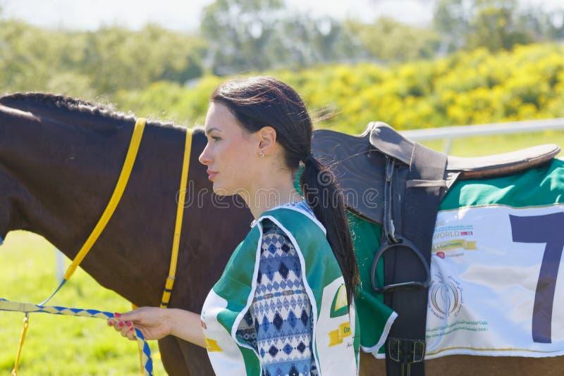 Красивая женщина водя лошадь гонки галопа аравийскую стоковые фото