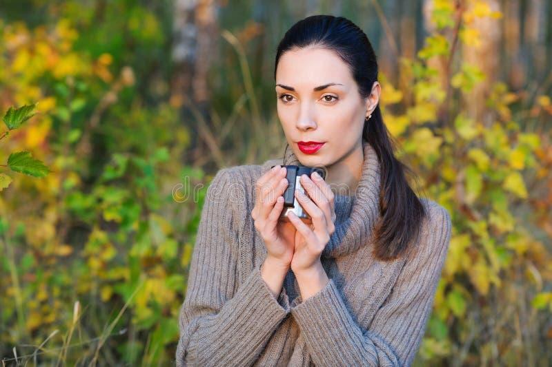 Красивая женщина выпивая горячий чай outdoors стоковое фото rf