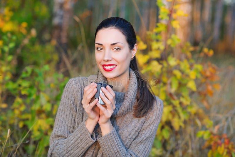 Красивая женщина выпивая горячий чай outdoors стоковое изображение
