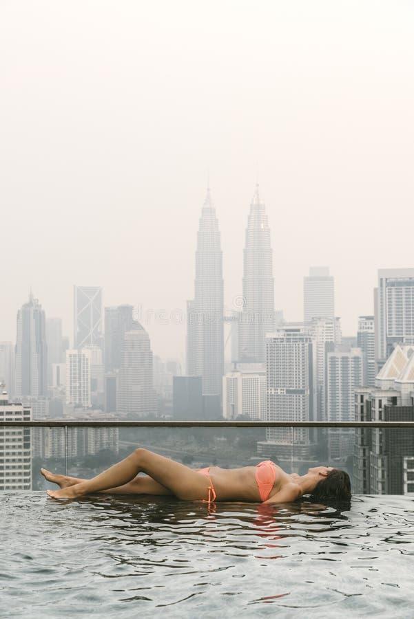 Красивая женщина в бассейне наблюдая город стоковое фото