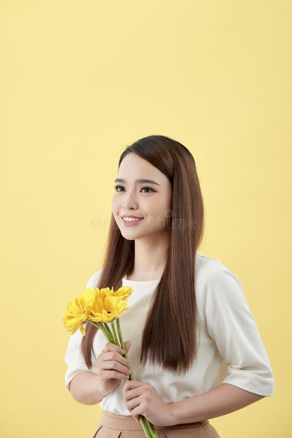 Красивая женщина в белой рубашке с gerbera цветков в руках на желтой предпосылке Она усмехается и смеется над стоковая фотография