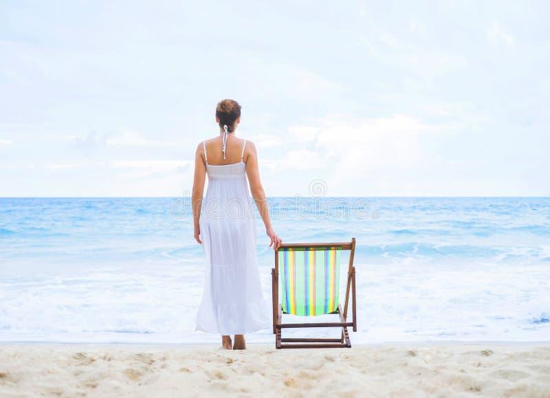 Красивая женщина в белом платье на пляже стоковое изображение