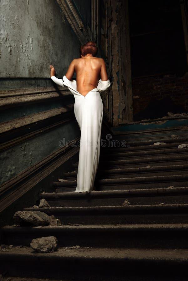 Красивая женщина в белом платье с нагой задней частью в дворце. стоковые фото