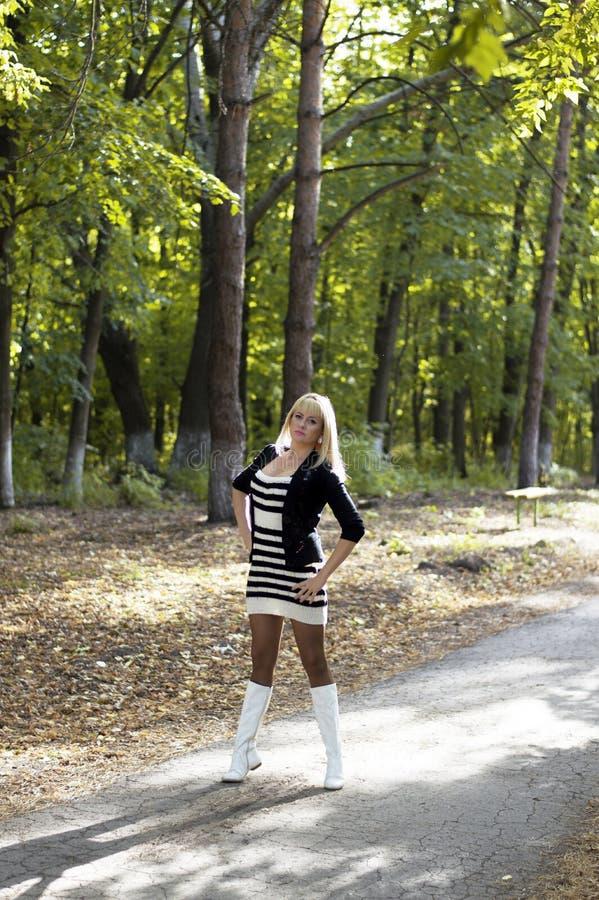 Красивая женщина в белых ботинках на следе леса стоковая фотография