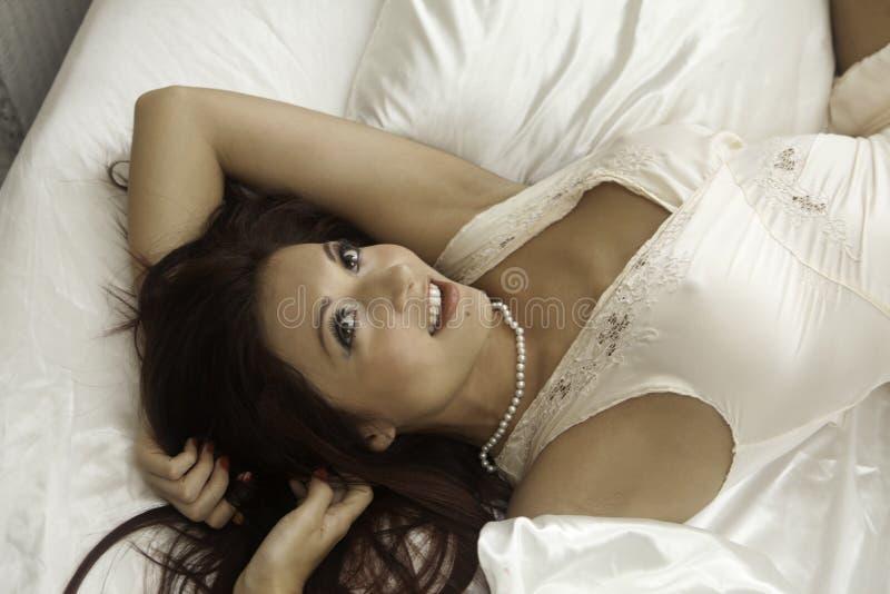Красивая женщина в ее спальне Стоковое Фото