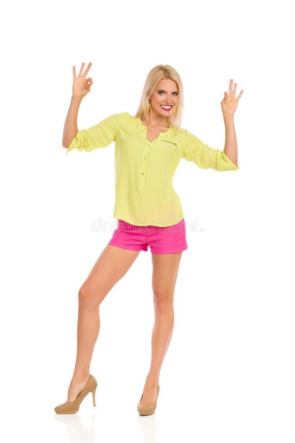 Красивая женщина в живых одеждах показывает знак и усмехаться руки ок стоковое изображение rf