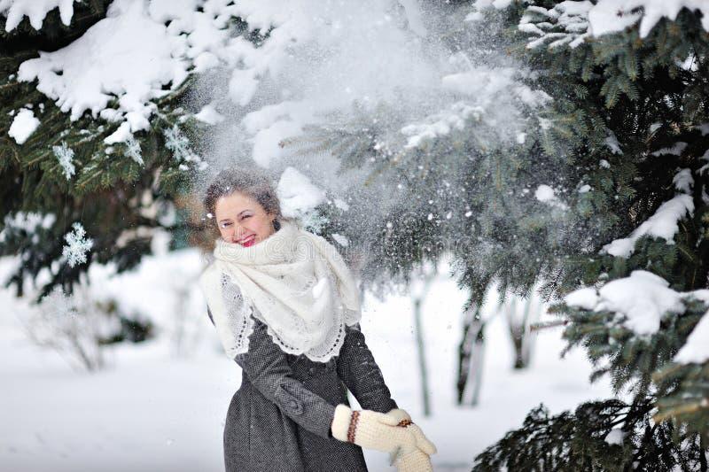 Красивая женщина в зиме связала снег ходов mittens стоковое изображение rf