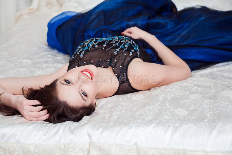 Красивая женщина в камере роскошного платья обольстительной смотря и зубастой улыбке, пока лежащ на белом покрывале кровати стоковые изображения