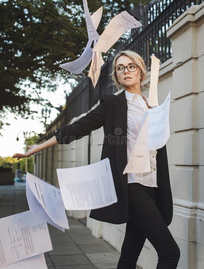 Красивая женщина в классическом костюме eyeglasses throuwing вверх по p стоковые фото