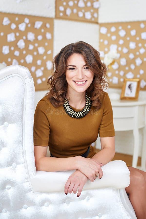 Красивая женщина в коричневом платье представляя на софе стоковое изображение